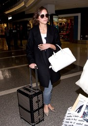 Marion Cotillard traveled in style with a Rochas leather tote and a Goyard suitcase.