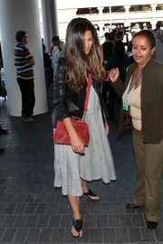Camila Alves added a pop of color with a red suede cross-body bag.