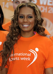Melanie Brown attended the International Fitness Week showing off long center part curls.