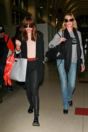 Dakota Johnson teamed her blazer with tight black leather pants.