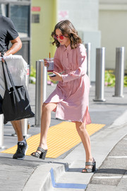 Millie Bobby Brown headed to 'Extra' wearing black and silver Alumnae mules and a pink shirtdress.
