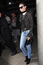 Miranda Kerr was rocker-glam in a black and gold ruffle blouse teamed with skinny jeans and patent boots as she arrived on a flight at LAX.