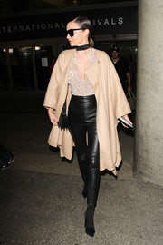 Miranda Kerr turned heads at LAX with this loose beige coat and black leather skinnies combo.