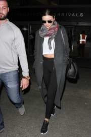 Miranda Kerr added some warmth to her crop-top and leggings combo with a gray wool coat while catching a flight.