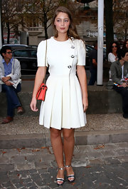 Marie-Ange Casta showed up at the Miu Miu Spring 2012 show in Paris wearing a strong-shouldered white day dress with large buttons and crisp pleats.