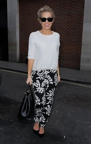 Mollie King chose a casual white crewneck to pair with her print pants.