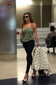 Nadine looked chic while traveling in a studded tank top, skinny jeans and white-hot peep toe pumps.