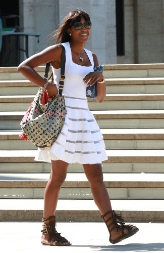 Naomi paired her fringe gladiator sandals with a printed canvas bag.