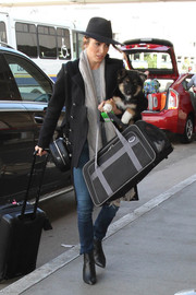 Nikki Reed had her hands full with a dog carrier duffle, a rollerboard, and her dog for the trip.