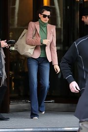 Penelope Cruz kept things casual in a pair of flared whiskered jeans and a rose blazer.