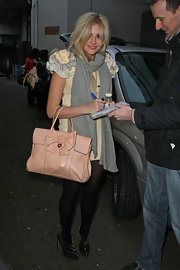 Pixie gave her edgy look a feminine touch with a soft pink bow embellished tote bag.