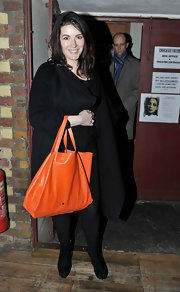 A tangerine colored tote brightened up Nigella Lawson's otherwise dark outfit.