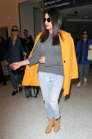Priyanka Chopra kept cozy in a gray crewneck sweater for a flight.