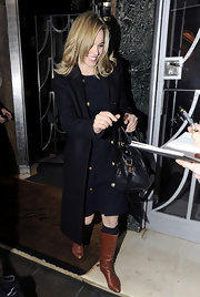 Rachel McAdams kept warm in her black dress thanks to cognac riding boots. She donned the flat boots over a pair of slouchy black knee high socks.
