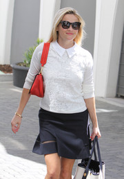 Reese added a pop of color with a bright red leather bag.