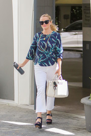 Reese Witherspoon headed out wearing a print blouse and flare jeans combo.