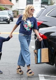 Reese Witherspoon went for summer-chic accessories, including a striped straw tote by Draper James.