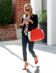 Reese Witherspoon added an extra pop of color with a pair of red Raye pumps.