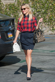 Reese Witherspoon donned a navy scalloped skirt that she paired with a tucked in shirt and simple, pointed heels .