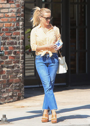 Reese Witherspoon matched her shirt with strappy orange platforms.