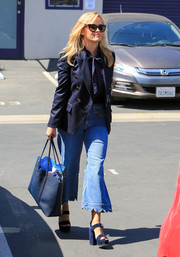 Reese Witherspoon topped off her look with a scalloped leather tote by Draper James.