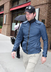 Bradley Cooper paired his zip up track jacket with a black logo hat.