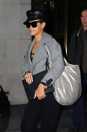 Rihanna attempts to go incognito with dark black wayfarers and this black leather captain's hat.