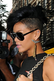 "Rihanna looked like a modern day rockstar with a buzzed faux hawk, oversized shades and a pair of chic dangling chain ""Hells Angel"" earrings."