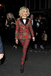 Rita Ora teamed lace-up boots with a plaid pantsuit, both by Moschino, for a head-turning look during the Rimmel London 180 Years of Cool party.