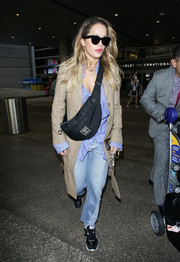 Rita Ora stayed warm in a grid-patterned beige coat during a flight to LAX.