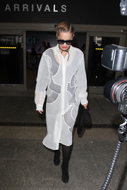 Rita Ora completed her airport look with a pair of mid-calf suede boots.