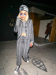 Rita Ora looked funky in a striped pantsuit teamed with a matching crop-top and beanie while enjoying a night out.