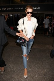 Rosie Huntington-Whiteley was spotted at LAX looking casual-chic in a white Dior bomber jacket and ripped jeans.