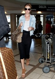 Rosie Huntington-Whiteley traveled in style with this light-wash denim jacket paired over a white tank.