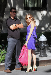 "SJP is Carrie Bradshaw! She is straight off the runway in this electric purple dress. She matched ""heated"" orange sunglasses with a grey lens that fades to orange. She knows how to play with color."