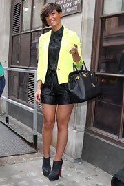 Frankie Sandford add a dash of color to her black romper when she paired it with this neon yellow blazer.