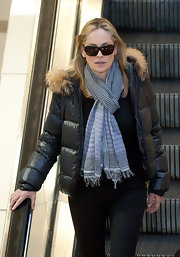 Sharon Stone wears a patterned plaid scarf with her puffer jacket for her travels at LAX.