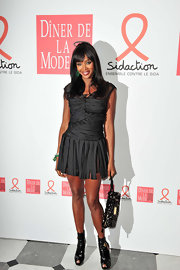 Naomi showed off her stylish ways in a pair of patent leather ankle boots. While the boots may be cute, they're probably not the best match to her ruched dress.