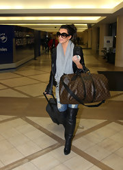 Miss Kardashian displayed her love of Louis Vuitton while traveling through LAX. Strutting her stuff in a pair of knee-high-leather boots she carried a huge LV monogram bag.