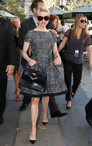 "This crocodile ""Kelly"" purse adds texture to her overall look and complements the black hemline of her dress."