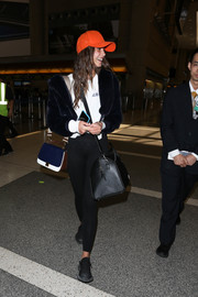Taylor Hill glammed up a simple white tee with a black fur jacket for a flight.