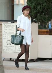Taylor Swift went shopping in Beverly Hills sporting a green leather tote, white shirtdress, and red hat combo.