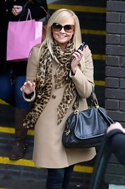 Emma Bunton added rich color to her stylish street wear with a teal leather purse.