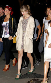 Taylor Swift kept her sweet vibe by layering a khaki collarless coat over her floral print dress.