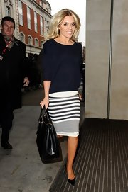 Mollie King chose a preppy look with this blue and white striped skirt and modest crewneck sweater.