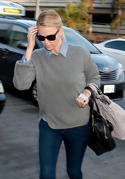 Charlize Theron layered a slouchy gray sweater over a prim chambray button up for a preppy look.