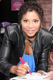 Toni Braxton signed autographs for fans wearing her short tresses in soft curls.