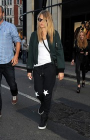 Cara Delevingne arrived for the Topshop Unique show looking sporty in star-print sweatpants and a zip-up jacket.