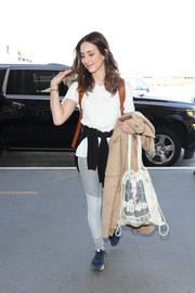Troian Bellisario sealed off her comfy airport look with a pair of blue New Balance sneakers.