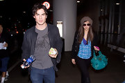 Ian wears a casual gray tee with his leather jacket.